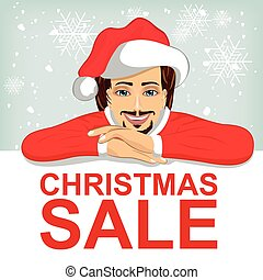 young man wearnig santa hat leaned on blank board with red christmas sale text