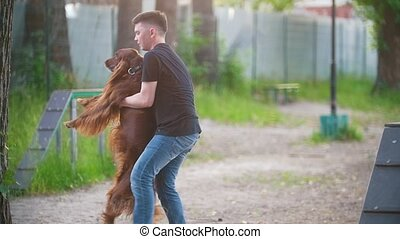 Young man whirling a dog irish setter in his arms outdoors...
