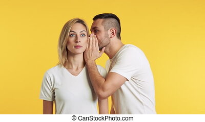 Young man whispering secrets to surprised woman over yellow ...