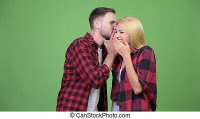 Young man whispering to young woman and laughing