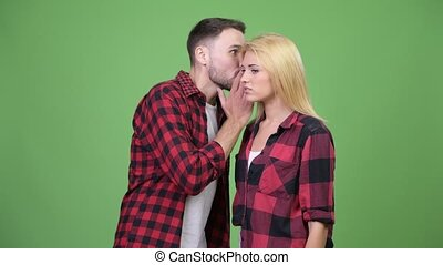 Young man whispering to young woman and looking shocked