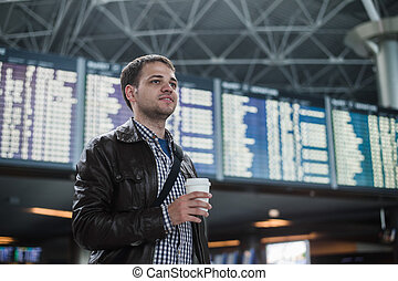 Young man with a bag in airport near flight timetable...