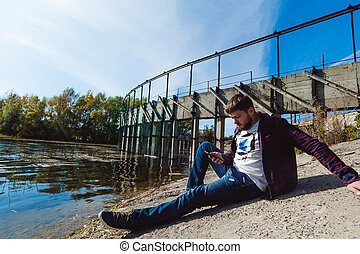 young man with a beard. a trip to the lake, an abandoned old dam, a warm sunny day. sits on the shore using a mobile gadget, a wireless network