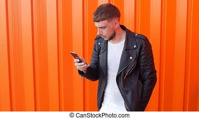young man with a beard in a black jacket looks into the phone on an orange background, slo-mo