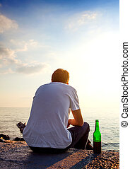 Man with a Beer - Young Man with a Beer sit at Seaside on...