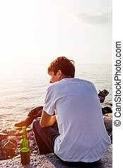 Young Man with a Beer sit at Seaside on Sunset Background