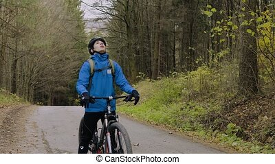 Young man with a bicycle outside in autumn nature.