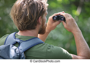 young man with a binoculars observing nature at the lake