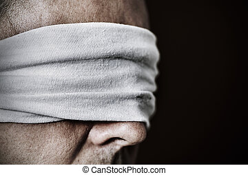 young man with a blindfold in his eyes - closeup of a young...