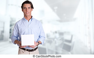 Young man with a box in a business background