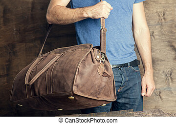Young man with a brown vintage travel bag