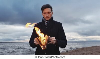 Young man with a burning book in hand standing on coast storm clouds on background