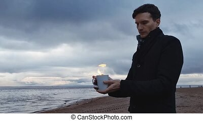 Young man with a burning cup in hand standing on coast storm clouds on background