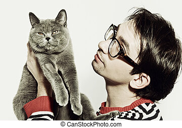 Young man with a cat in her arms