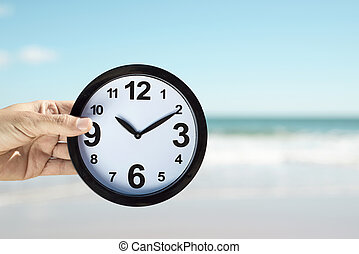 young man with a clock on the beach