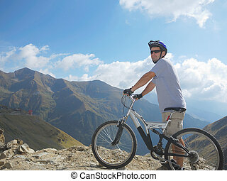 young man with a full suspension bike in mountains ...