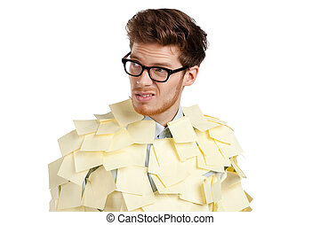 Young man with a glasses covered with yellow sticky notes, isolated on white background