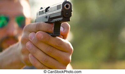 Young man with a gun is aiming to shoot a close-up