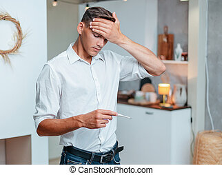 young man with a headache measuring the temperature.