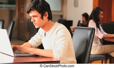 Young man with a laptop in a canteen
