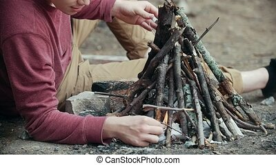 Young man with a match lights a branches for the campfire in...