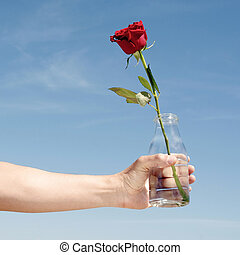 young man with a red rose in a glass bottle
