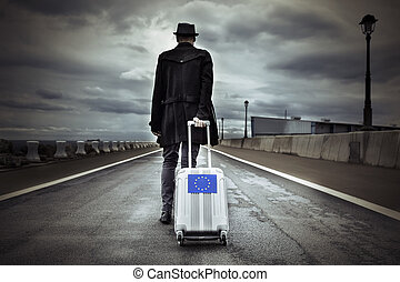 young man with a rolling suitcase with an European flag - ...