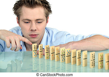 Young man with a row of dominoes