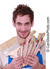 Young man with a selection of decorating paint brushes