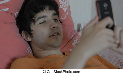 Young man with a smartphone lying on a bed