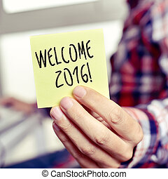 young man with a sticky note with the text welcome 2016 -...