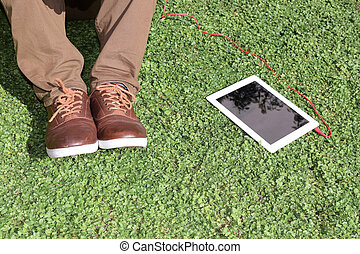 Young man with a tablet in the park