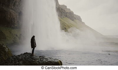 Young man with action camera standing close to Gljufrabui waterfall in Iceland and filming video of stream of water.