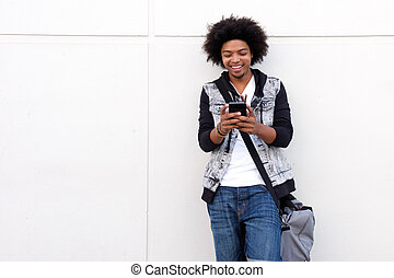 Young man with afro looking at cell phone