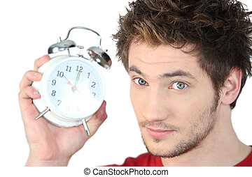 Young man with an alarm clock