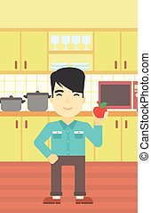 Young man with apple in the kitchen.