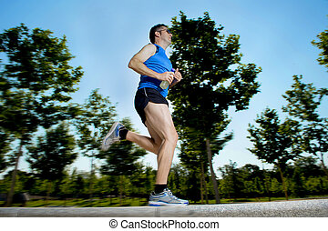 young man with athletic runner legs holding isotonic energy drink while running in city park