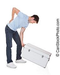 Man With Back Pain Lifting Metal Box