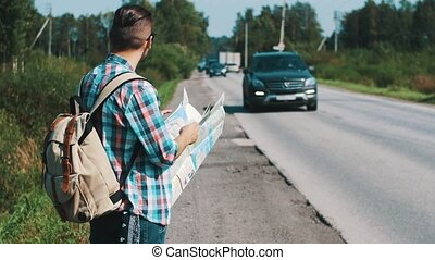 Young man with backpack hitchhiking at road in countryside. Map. Thumbing up