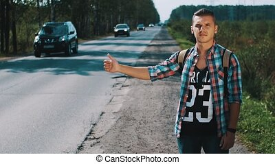 Young man with backpack hitchhiking at road in countryside. Thumbing up. Travel