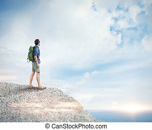Young man with backpack on the rock. Visual effects -...