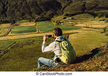 young man with backpack photographing beautiful icelandic landscape