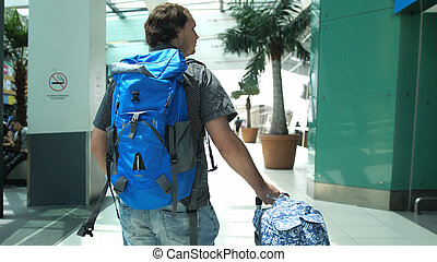 Young man with backpack pulling suitcase in modern airport terminal. Travelling handsome guy walking away with his luggage