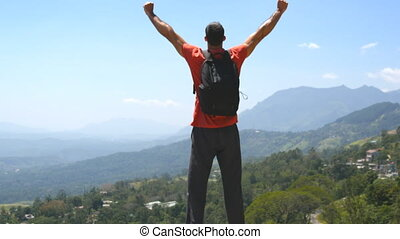Young man with backpack reaching up top of mountain and...