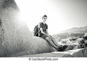 young man with backpack resting