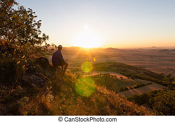Young man with backpack sitting on hill and looking to Czech ore mountain valley at sunrise. Czech landscape