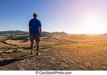 Young man with backpack standing on hill and looking to Czech central mountain valley at sunrise. Czech landscape
