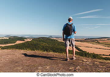 Young man with backpack standing on hill and looking to Czech central mountain valley at sunrise
