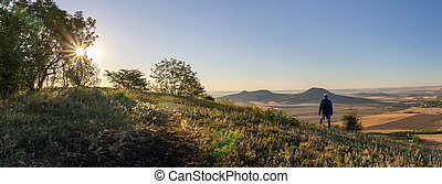 Young man with backpack standing on hill and looking to Czech central mountain valley at sunrise. Panoramic landscape