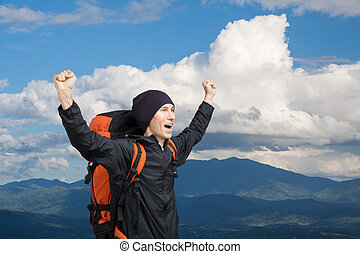 Young man with backpack standing on top of a mountain with his hands up.